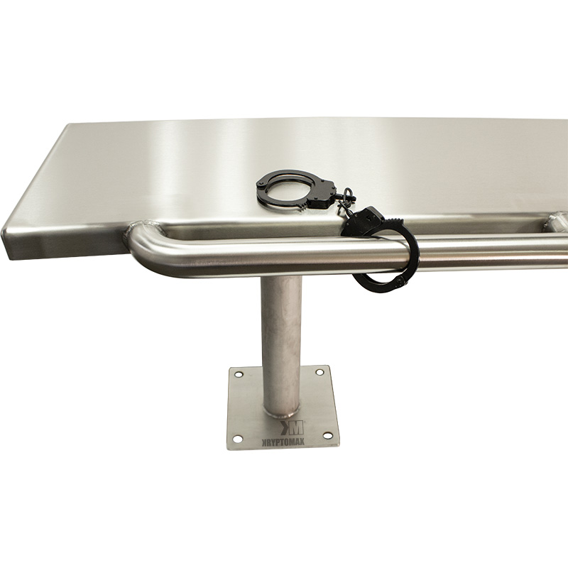 Black pair of handcuffs shown attached to restraint bar on front of the KryptoMax® Stainless Steel Floor Mounted Detention Bench
